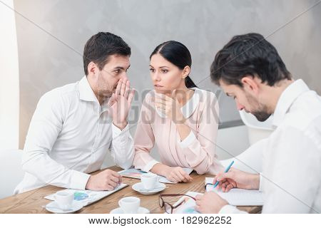 Business meeting. Business team discussing strategy. Businessmen and woman in luxury restaurant. They having coffee. Man and woman chitchatting about another man
