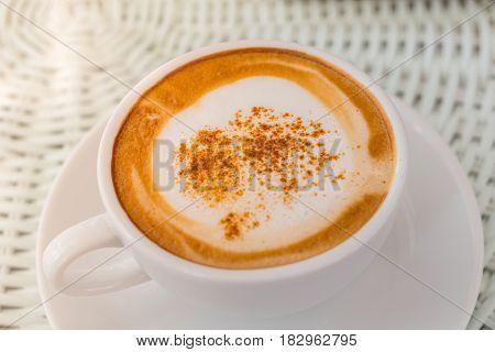 Hot cappuccino coffee in white ceramic glass