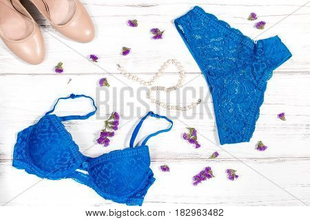 Blue lacy lingerie set with pearl necklace and nude shoes on a white wooden background with violet flowers scattered around