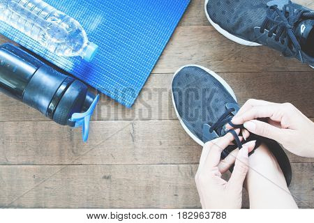 Active female hand with sport and working out equipments flat lay on wooden floor