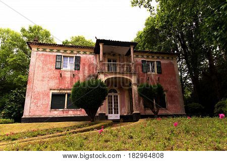 Abandoned and dilapidated mansion in a beautiful and well-groomed Park in the shade of the trees