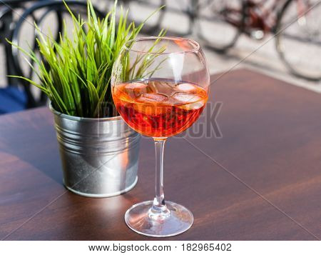 travel to Italy - glass of Spritz cocktail with ice on table in outdoor cafe in Padua city in spring