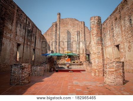 Ancient Church with old brick and Buddha statues. and Blue sigh with Thai languate with