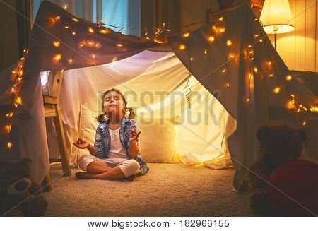 child girl playing meditates in yoga pose in tent at home before going to bed