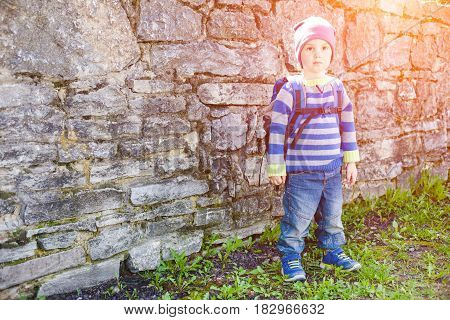 Boy With Backpack Standing Near A Stone Wall.