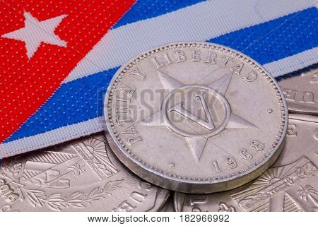 Detail of different Cuban pesos coins on the table.