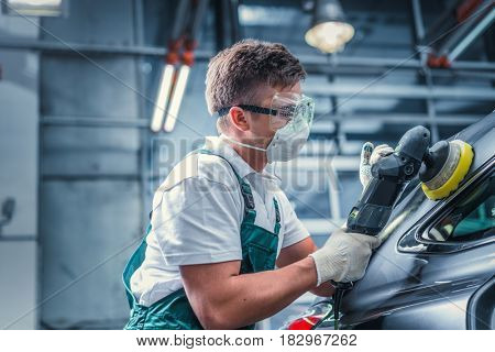 Young man polishing car in service