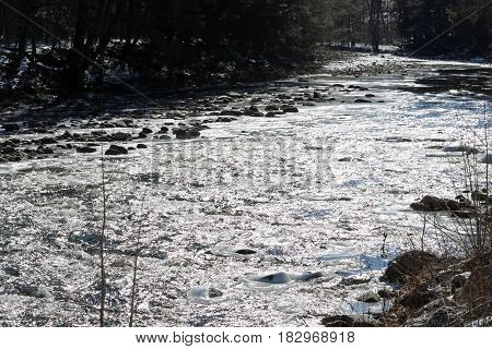 Loyalsock Creek rapids in the sun and shadows with boulders and ice.