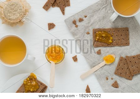 Sweet Snack Or Breakfast With Rye Crisp Bread (swedish Crackers), Spread Orange Jam, Cups With Green