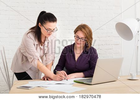 Middle-aged women in office. Teamwork, business communication. Discussing project. Start up solutions. Female coworkers.