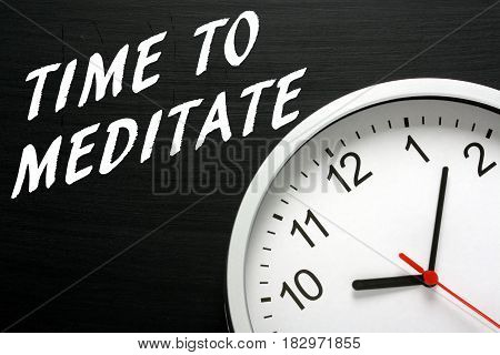 The words Time to Meditate written on a blackboard next to a modern wall clock as a reminder to set aside time for meditation and relaxation