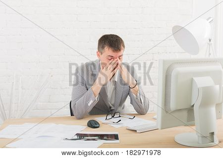 Overworking, toried at work. Young businessman in white modern office interior, sitting at his desk