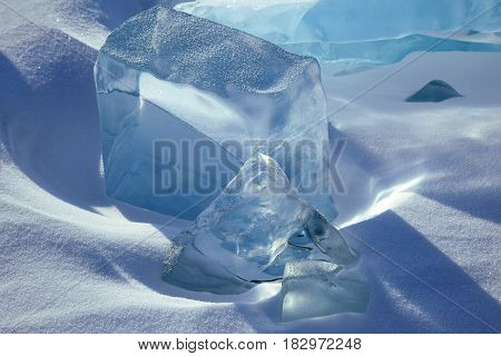 Geometrical formations of blue ice in snow cube shaped block and pyramid shaped block