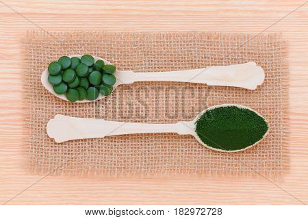 superfood seaweed spirulina and chlorella pills and powder on wooden healthy lifestyle