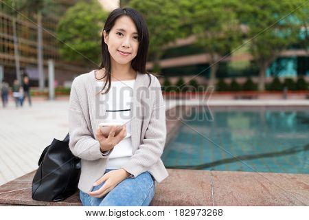 Woman holding cellphone at outdoor