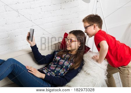 Children in eye glasses look into tablet. Computer games, social networks and media addiction concept. Girl and boy with tablet. Eyesight, eyewear for kids.