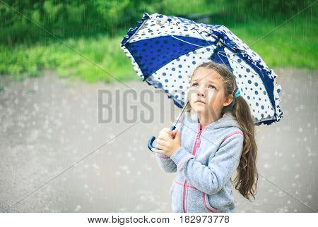 Portrait of a cute sad girl with an umbrella in the rain.