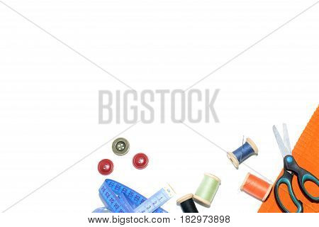 Coil with thread scissors and ruler on a piece with a bright cloth on a white background.