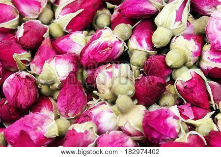 Dry red and pink rose buds, healthy herbal tea background.