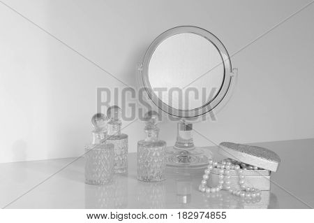 little mirror on a dresser rounded with fragrance bottles and casket with pearls
