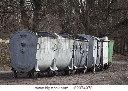 Row of wheeled steel trash containers outside