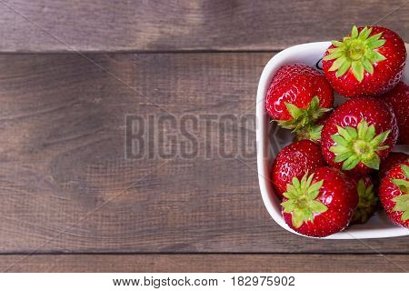 Strawberry on a dark wooden background. Berries of a strawberry in a white bowl. Summer banner. Vegan food. 	Garden strawberry.