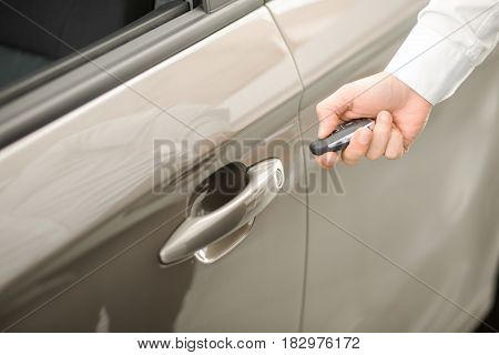 Young man standing near the car opening door rental service