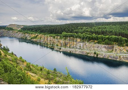 Beautiful summer industrial landscape. Flooded quarry limestone. Russia Ural