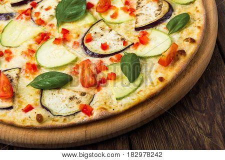 Delicious italian vegetarian pizza closeup, with cherry tomatoes, peppers, aubergines and zucchini - thin pastry crust at wooden table background