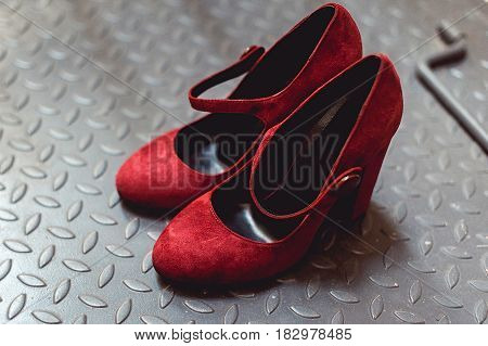 Ladies red chamois leather pumps shoes on a metal background, close up.