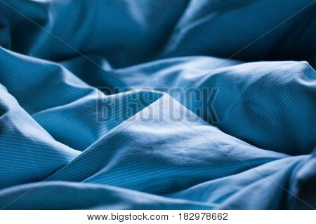 Gently sleeping blue bed sheet in soft morning or evening romantic sunlight as beautiful textile sleep relaxation decorative night background