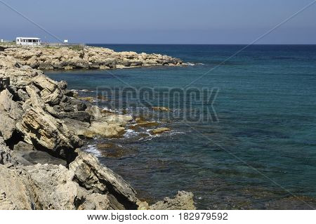 Eroded volcano stone at the beach and clear blue water and blue sky outside the village Lapta in the North of Cyprus
