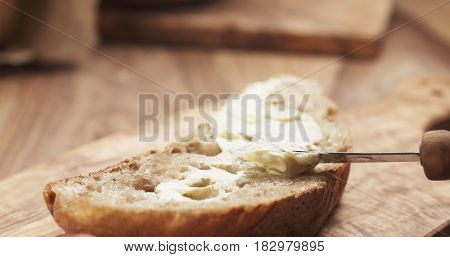 female teen hand spreads butter on slice of rustic bread, 4k photo