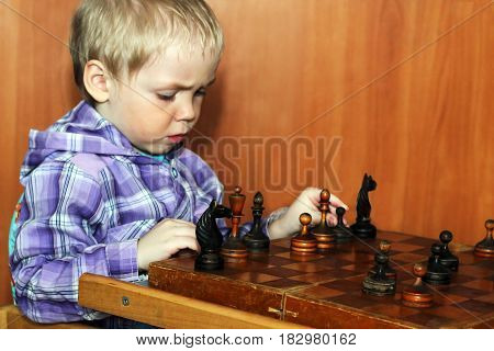 Little boy playing in old chess retro game