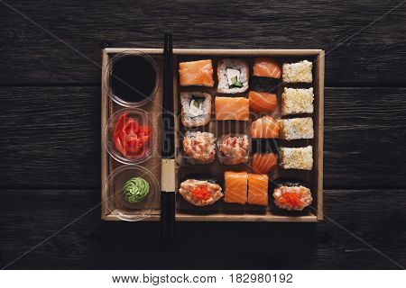 Japanese food restaurant take away in craft carton, sushi maki gunkan roll plate or platter set. Chopsticks, ginger, soy sauce, wasabi. Meals at rustic wood background in delivery box. Top view.