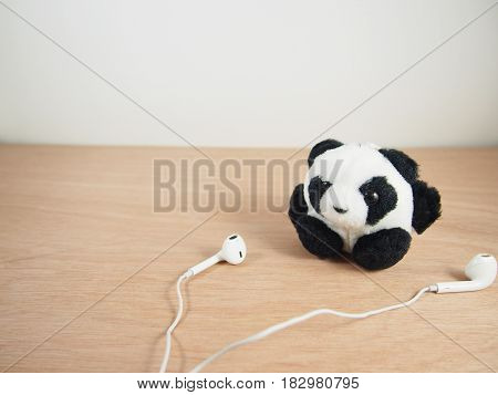 Round fat panda with white earphones on wooden background