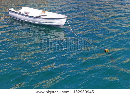 little white rowing boat anchored in blue and green water sunlight reflections
