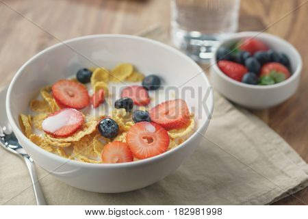 healthy breakfast with corn flakes and berries in white bowl, slightly toned photo