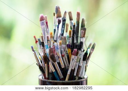 Set of color messy paint brushes in metal tin can on the window with green background as art creative innovative imagination hobby craft tool concept