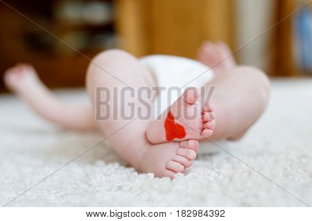 Feet and legs of newborn baby with diaper. Cute little girl or boy two months old Dry and healthy body and skin concept. Baby nursery. Red heart on tiny foot