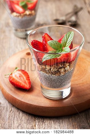diet healthy breakfast. chia pudding strawberries and muesli in a glass fresh strawberry on old wooden background