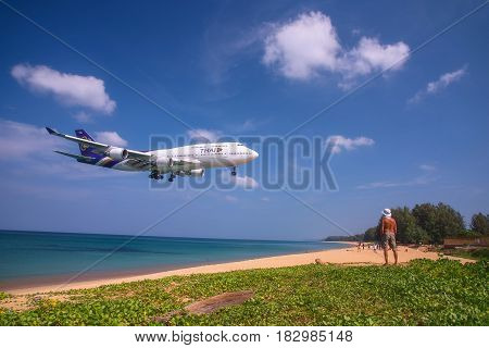 PHUKET THAILAND - MARCH 04 2017: Unidentified Man looking the plane was landing phuket international airport near Mai Khao Beach on Phuket Island in Thailand.