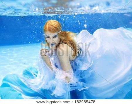 Underwater fashion portrait of beautiful blonde young woman in blue dress