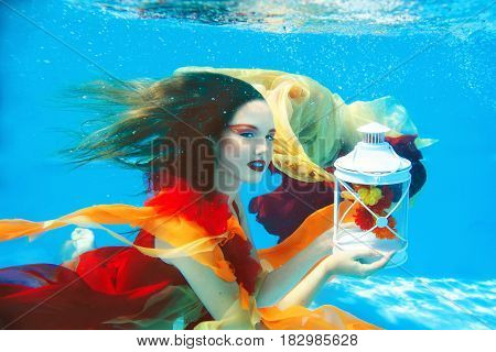 Underwater fashion portrait of beautiful blonde young woman in red dress with lamp