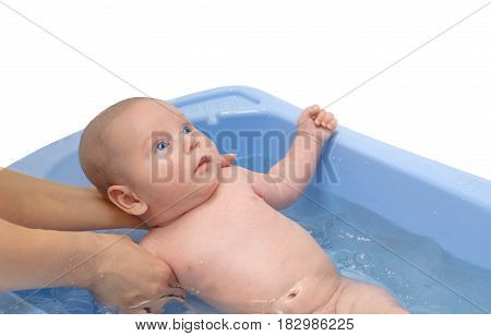 Mother washing a newborn baby in blue bathtub isolated on white