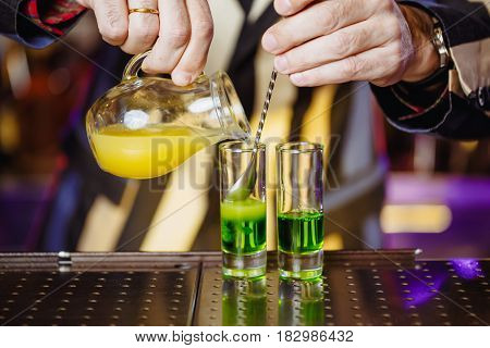 A real cocktail shot of a green Mexican with banana liqueur lemon juice and tequila. Cooking at the bar nightlife. Horizontal photo