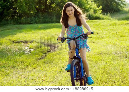 A teenage girl is riding a bicycle on the lawn. The picture was taken in summer in nature.