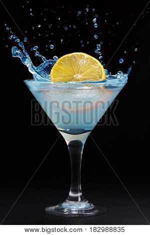 A splash from a lemon in a martini glass on a black background