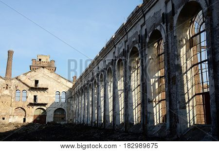 Ruins of old abandoned plant with gas furnace chimney and broken windows, Odessa, Ukraine, Europe
