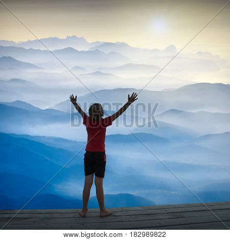 Young boy standing above the misty mountain valley with raised hands in a light of rising sun.
